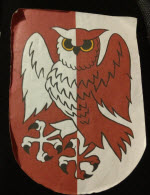 Device: Per pale gules and argeant an owl rising countercharged.