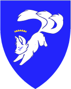 Device: (Fieldless) A three-tailed fox sejant erect argent charged on the shoulder with an annulet azure.
